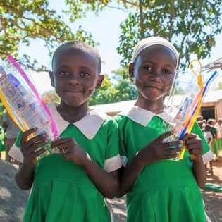 Dala Development - Students with kits of a toothbrush, paste, floss, and a toothbrush cover