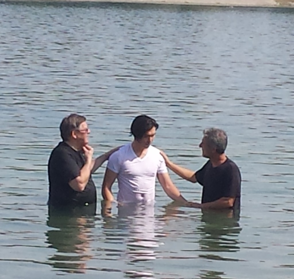 MIhal and Arish (former persecuted refugee) provide baptism for a refugee.