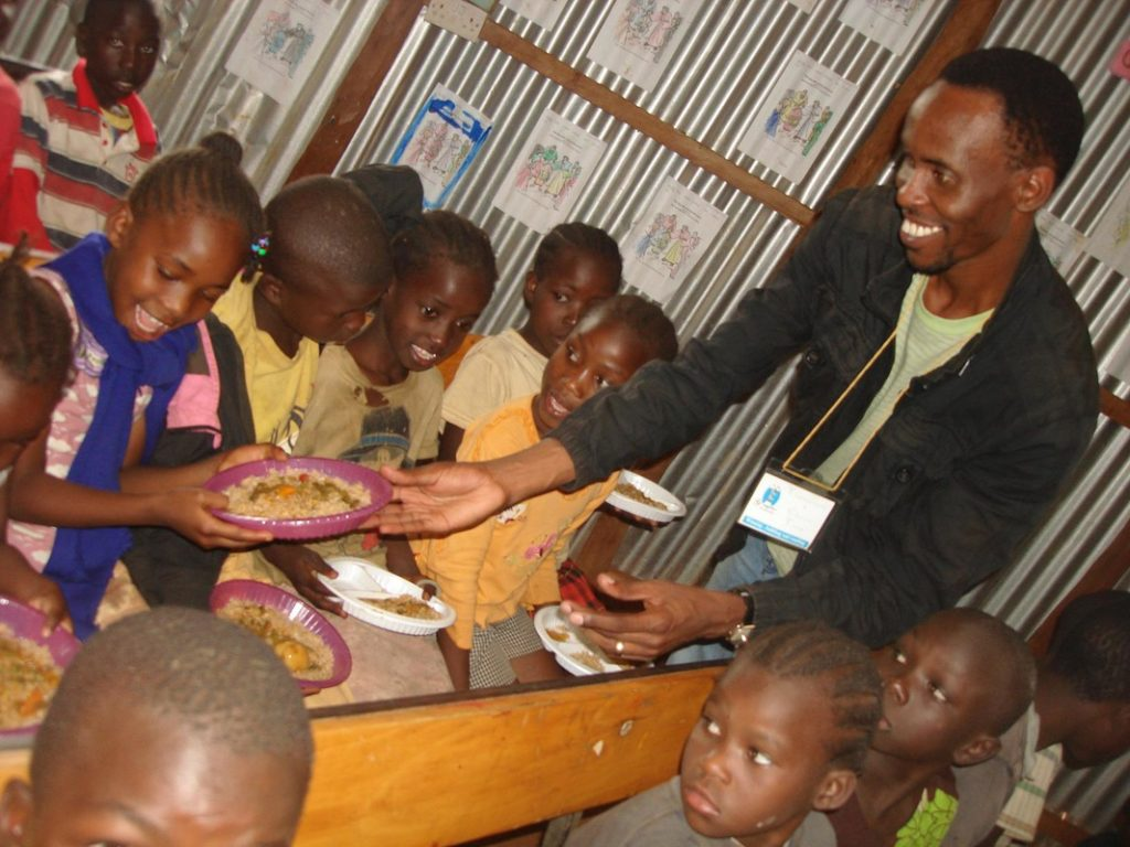 Youngster for Christ Team - Sammy sharing food with school children