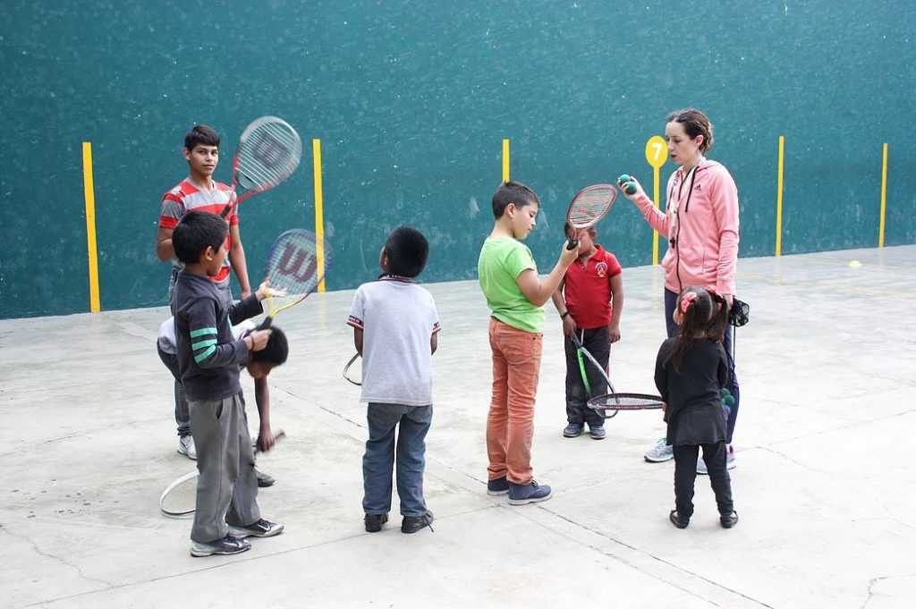 Instructor Nancy teaches tennis to a group of children from Restore.
