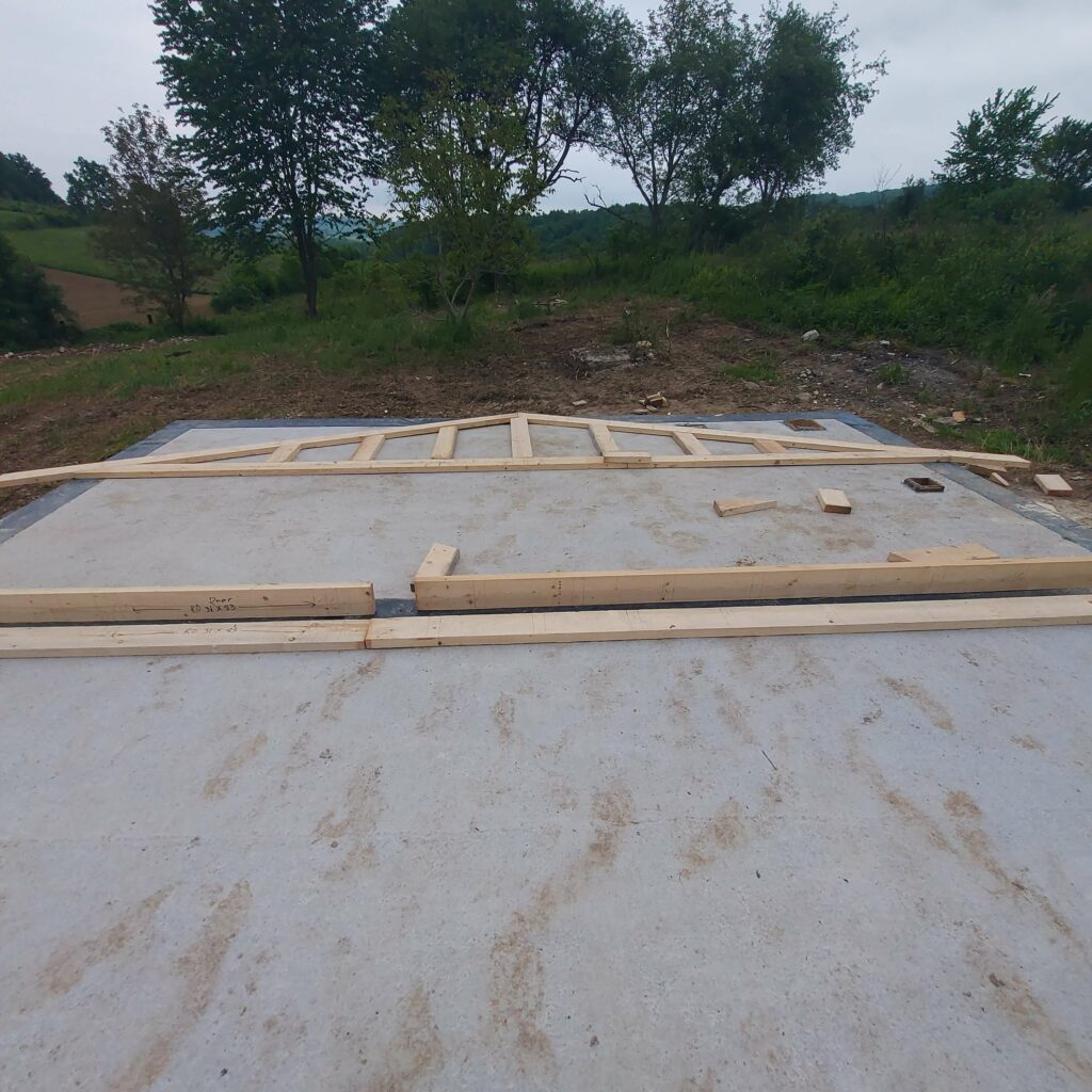 Laying out the building plans on the concrete slab.